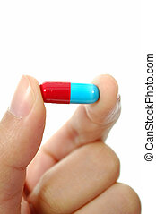 Medication - Blue and red capsule between two fingers