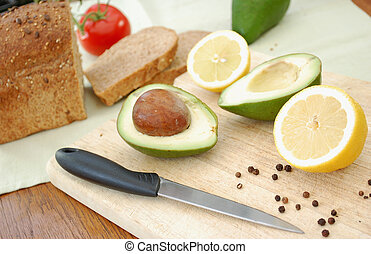 Healthy food preparation - Sliced avocados and lemons on a...