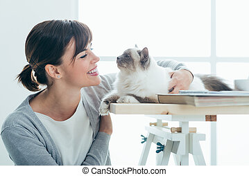 Happy woman cuddling her cat - Happy smiling woman at home...