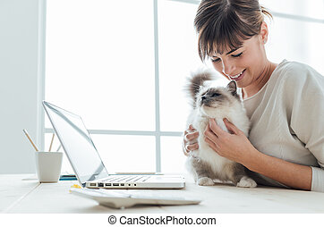 Woman cuddling her cat - Young woman sitting at desk and...