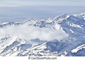 Snowy mountains at Andes Cordillera with some clouds...