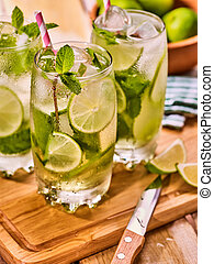 On wooden boards is glasses with mohito and knife. - Alcohol...