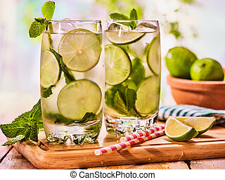 On wooden boards is glass with mohito and lime. - Alcohol...