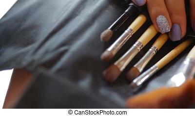 Makeup Brushes and female hands with manicure