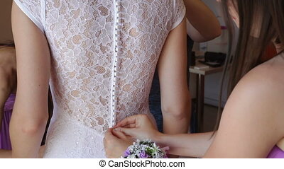 bridesmaid tying buttoning wedding dress - bridesmaid tying...