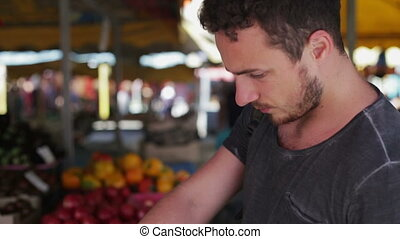A man buys vegetables at a market the day