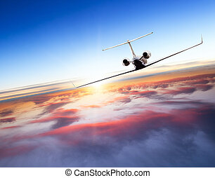 Private jet plane flying above clouds in beautiful sunset....