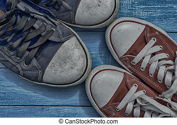 two pair of old worn sneakers on a blue shabby floor