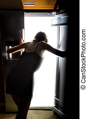 Late Night Snacking - Woman craving and looking for food in...