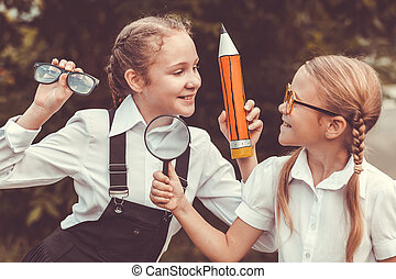 Smiling young school children in a school uniform against a...