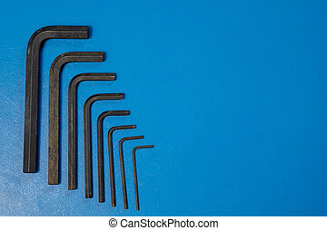 Hex key wrench set on blue table .