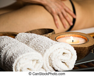 Young woman receiving a cellulite massage in the spa salon. close-up candle and towels
