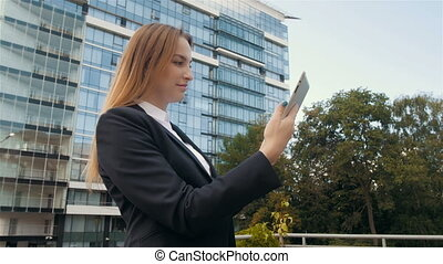 Portrait of Beautiful Business Woman Using Tablet PC Outside...