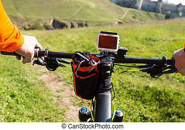 Hands in orange jacket holding handlebar of a bicycle