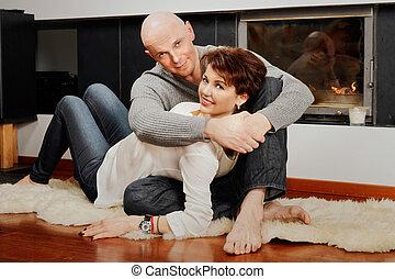 Beautiful pair sitting on fur carpet near fireplace -...