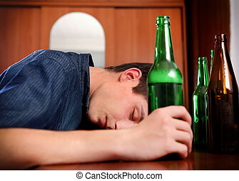 Young Man sleep with a Beer - Tired Young Man with Bottle of...