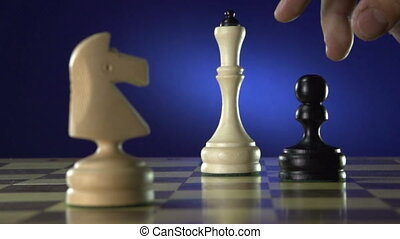 Black chess player knocks down the white king with his piece