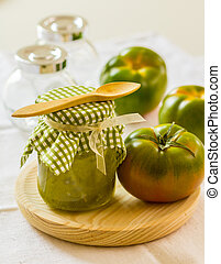 Green tomato chutney in a jar on a wooden surface