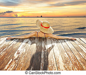 Woman at beach - Woman in hat relaxing at beach jetty