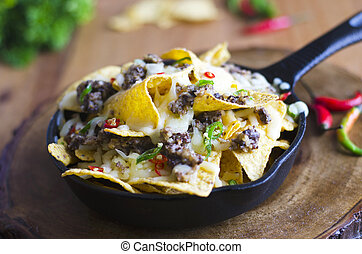 Nachos with haggis, melted cheese and chilli peppers