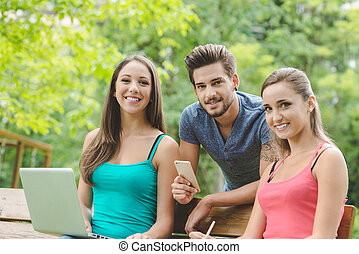 Teenagers at the park studying together - Teenager guy and...