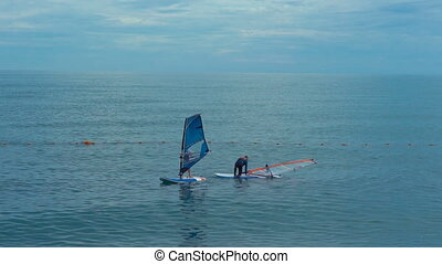 Windsurfing beginners taking the first steps in learning -...