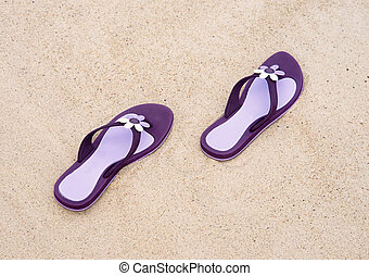 Close-up of purple flip-flops on the sand - Close-up of...