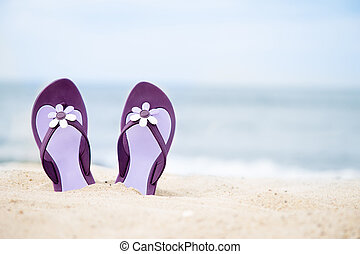 Beautiful, purple flip-flops on the beach on a sea...