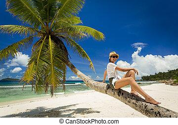 Relaxing On Palmtree - Beautiful woman sitting on a palmtree...