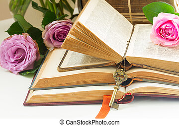 Old books with rose flower - Pile of vintage old books with...
