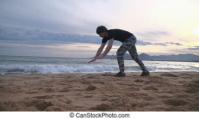 Young man doing acrobatic tricks on the beach - Young man...