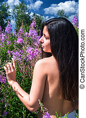 beautiful nude woman relaxing on meadow. Back view -...