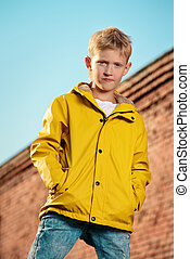 yellow raincoat - Cool modern eight-year boy posing over...