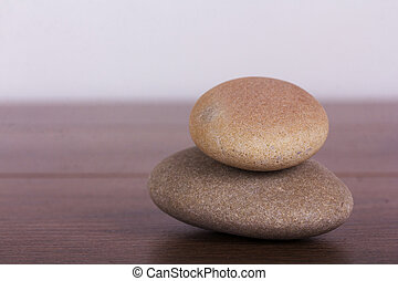 Stacked pebbles on a rustic wooden background