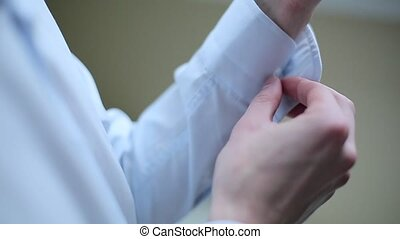 Man buttoning cufflinks on white shirt.