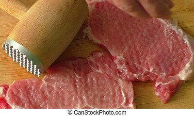 Pork steaks - Tenderization of fresh pork steaks on wooden...