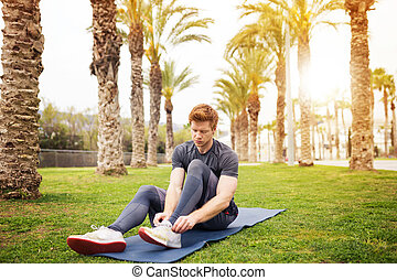 Man tying his shoelaces - A photo of young, sporty man...