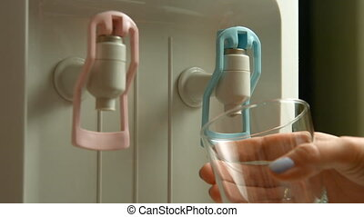 Filling cup at water cooler, water dispenser - Woman filling...