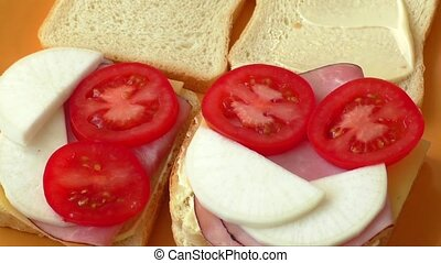 Making sandwich with tomato, ham, cheese, radish, mayonnaise