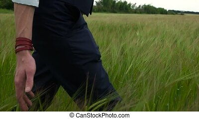 man in suit walking ghrough the green field