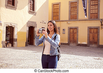 Pretty young girl taking touristy pictures while smiling a...