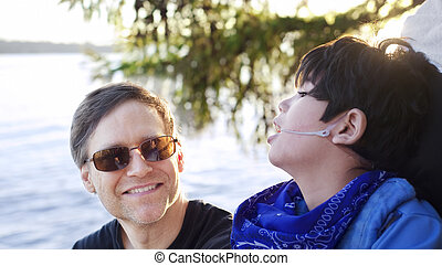 Father talking with disabled son in wheelchair at lake