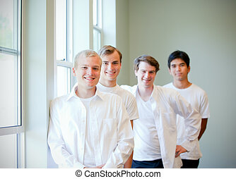 Young groom standing with groomsmen, getting ready for...