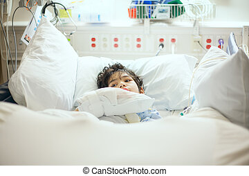Disabled little boy lying sick in hospital bed