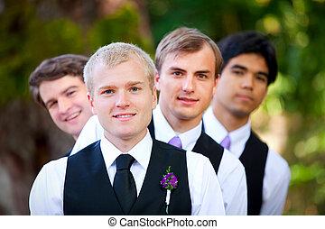 Groomsmen peeking from behind groom, outdoor - Groomsmen...