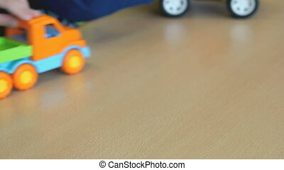 Children play toy model cars at the table at the nursery