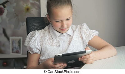 Little girl holding a digital tablet computer sits at the...