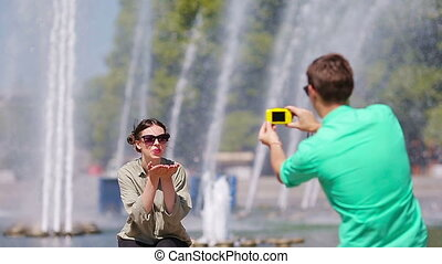 Boyfriend taking a picture of his friend while sitting background the fountain. Young man making photo of woman on the street laughing and having fun in summer.