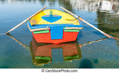 Brightly painted dinghy reflected in water - Brightly...