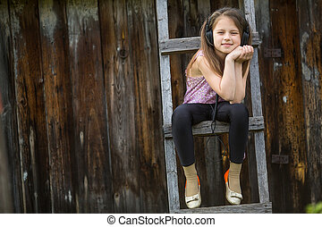 Little naughty girl with headphones sitting on a wooden...